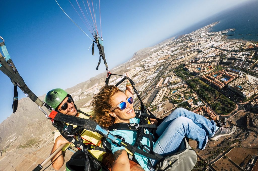 Ulraub-Fewo_0010_Cheerful-happy-woman-to-paraglyde-experience-with-pilot---couple-having-fun-in-the-air-paraglyding-over